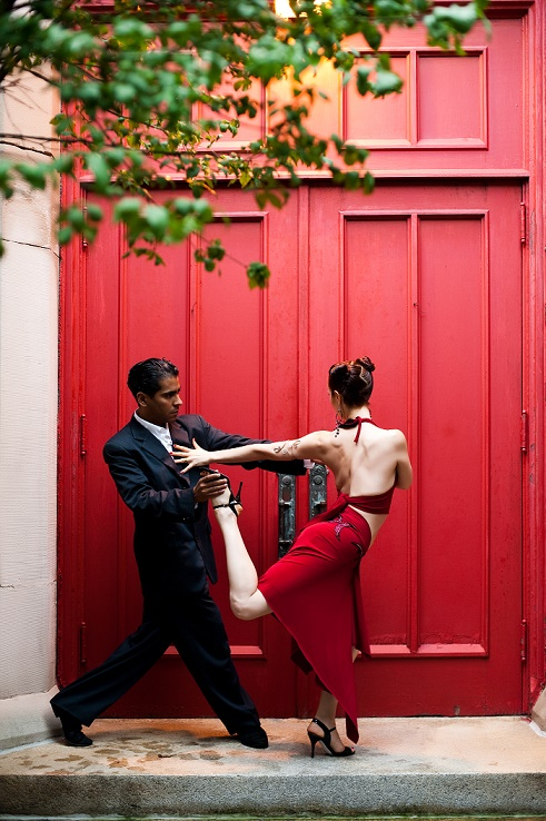 A man in a black suit and a woman in a red dress dance the Tango together.